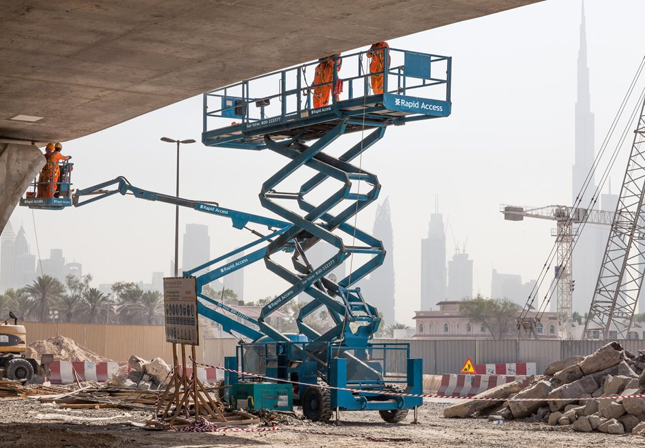 Manlift Genie AWP boom and scissor working on Dubai Water Canal UAE, Burj Khalifa in background